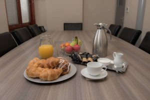 croissants-fruit-coffee-and-juice-on-meeting-table